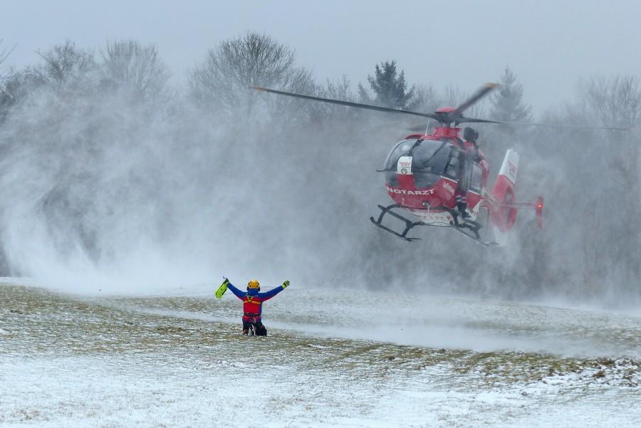 Windenübung bei Schnee in Enzendorf im März 2018. Ein Bergwachtmann weist Christoph 27, D-HDRU, bei der Landung ein.