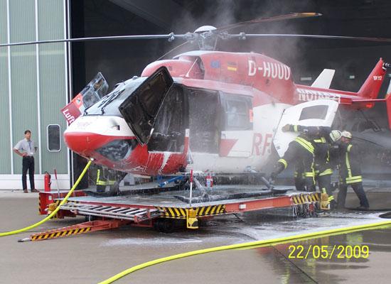 Feuerwehrmänner der Flughafenfeuerwehr Stuttgart untersuchen den Hubschrauber
