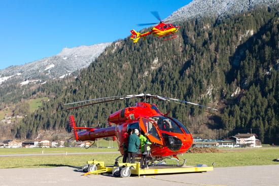 """Während der Helikopter von Knaus am Boden steht, landet """"Heli 4"""" im Hintergrund"""