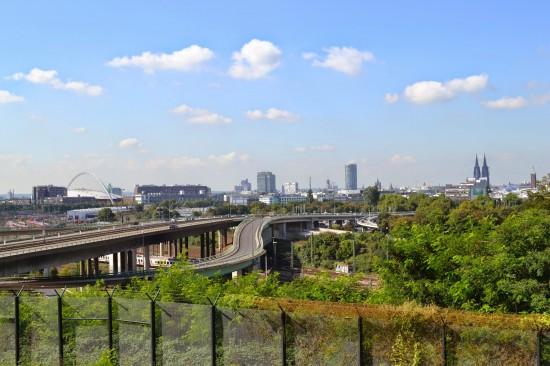 Blick vom Landeplatz über die B 55a Richtung Südwesten (Stadtteil Deutz und im Hintergrund die Innenstadt) mit dem Absperrzaun im Vordergrund.