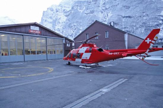 """Eine Agusta A109 als """"REGA 12"""" vor dem Hangar - gut zu sehen die Kooperation mit der """"Heli-Linth AG"""", deren Name als Beschilderung auf der Halle angebracht ist"""