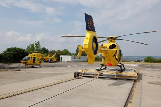"""Die RTH-Crew ist während den Umbauarbeiten in Containern untergebracht (rechts RTH """"Christoph 23"""", links Dual-Use-RTH """"Christoph 77"""" mit der Ersatzmaschine D-HLTB)"""