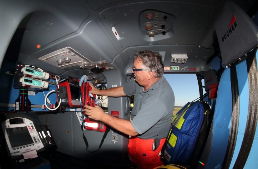 Ein Besatzungsmitglied rüstet die Kabine der H135 mit dem medizinischen Gerät aus