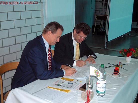 Helmut Büschke, Geschäftsführer der Elbe-Helicopter, und Rüdiger Unger, Präsident des Vorstandes des Landesverbandes DRK Sachsen unterzeichnen im Hangar des LRZ Bautzen den Kooperationsvertrag