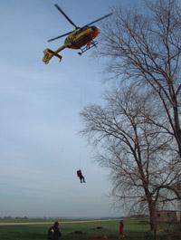 Luftretter Matthias Riffer seilt sich zur Einsatzstelle hinunter. Der HCM beobachtet das Abseilen des Luftretters. Der Pilot kann den Luftretter und die Absetzstelle im Spiegel sehen