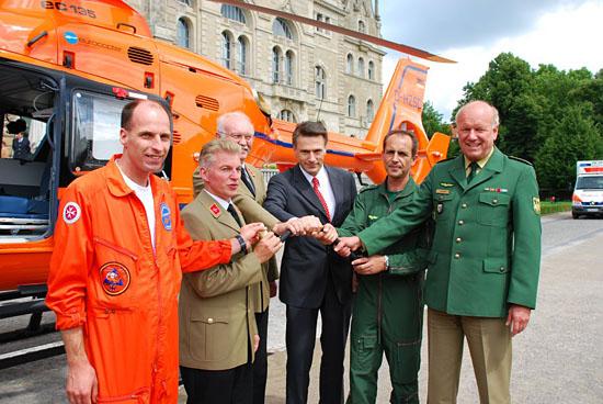 Handshake der Beteiligten; in ihrer Mitte der Eurocopter-Steuerknüppel