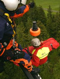 Bergungstrage an der Seilwinde; der Windenoperator hat das Bedienelement in der rechten Hand; er steuert und koordiniert den Vorgang