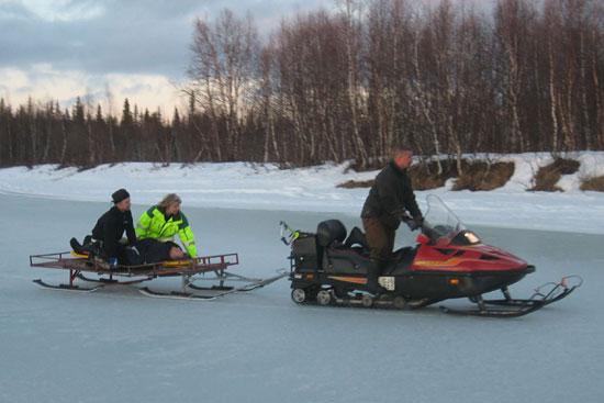 Patient auf dem Spineboard mit Hubi-Rettungsassistentin Britta. Transport zum Hubi mit dem Snowmobil