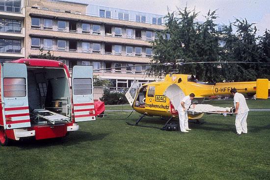 """Bevor die Hangaranlage vor dem Klinikgebäude in Betrieb genommen werden konnte, fand der Flugbetrieb vom Park des Unfallklinikums aus statt. """"Christoph 2"""" hier neben dem """"NAW 2"""" der BF Frankfurt."""