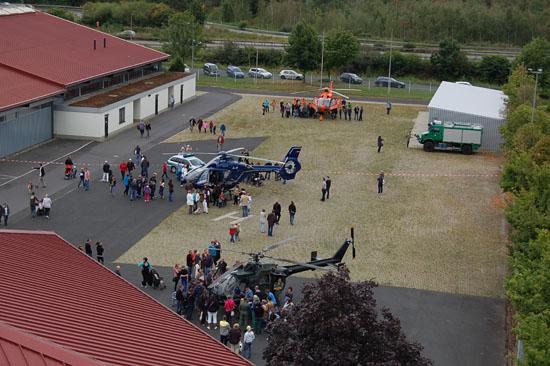 Aus großer Höhe fotografiert: das Freigelände der Kasseler Messehallen mit den drei dicht umringten Hubschraubern von Bundespolizei (2-mal EC 135) und Bundeswehr (Bo 105)