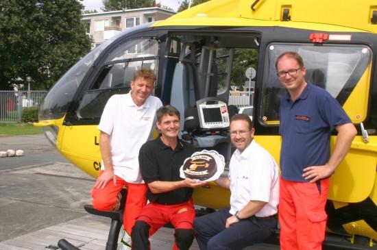 HCM Heiko Haase, Stationsleiter Rüdiger Engler und ltd. Hubschrauberarzt Dr. Andreas Callies freuen sich über eine Jubiläumstorte