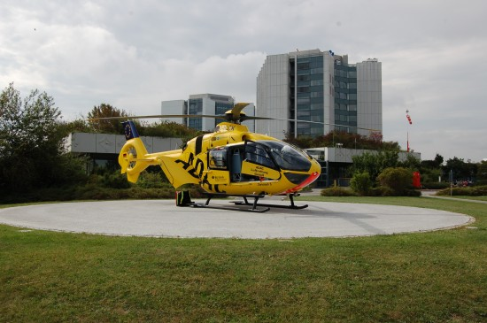 """Der RTH """"Christoph 5"""" steht vor dem imposanten Bau der Berufsgenossenschaftlichen Unfallklinik Ludwigshafen"""
