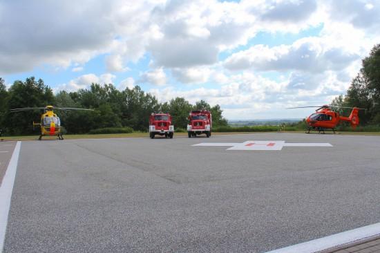 Für ein Fotoshooting wurden die Oldtimerfahrzeuge der Freiwilligen Feuerwehr Winsen zwischen beiden Hamburger Rettungshubschraubern positioniert