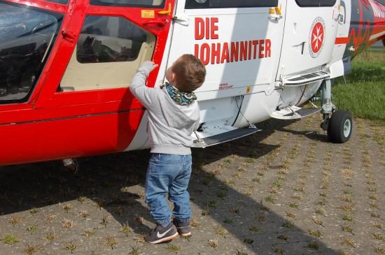Während Gerd Schröder als junger Sozi am Zaun des Kanzleramtes rüttelte, versucht es der kleine Junge mit der Tür des Intensivtransporthubschraubers