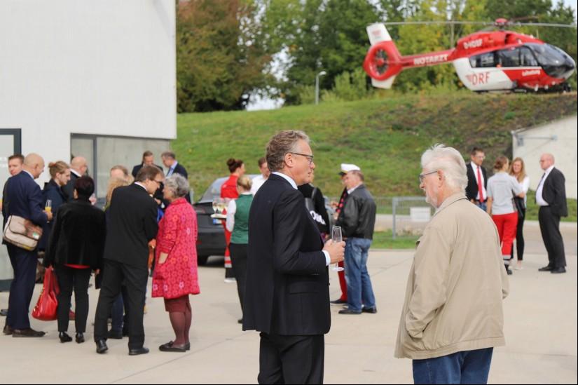 """Gäste aus den unterschiedlichsten Bereichen fanden sich für einen Sektempfang am Hangar ein, im Hintergrund die Einsatzmaschine """"D-HDSF"""" auf dem oberen Helipad."""