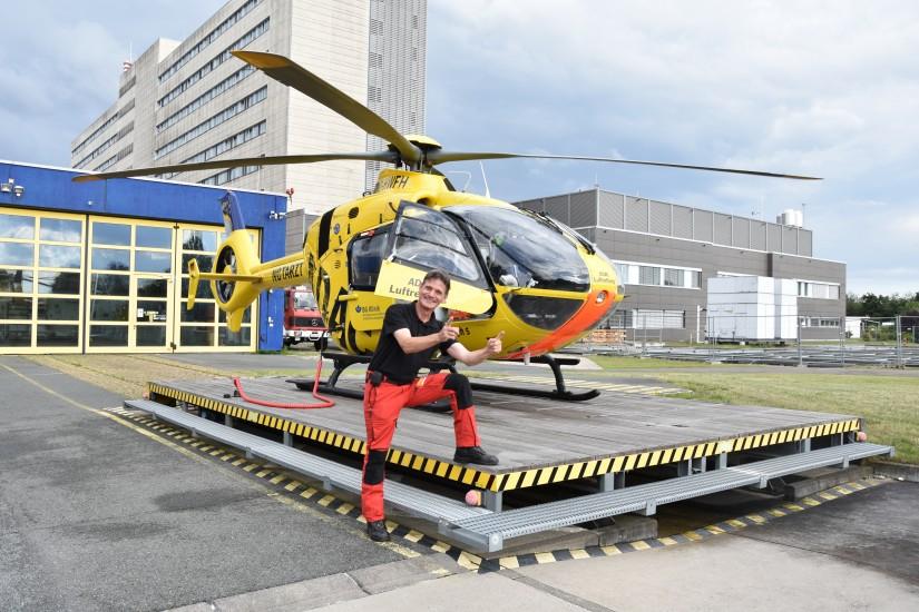 """Rüdiger Engler, Stationsleiter und Pilot des RTH """"Christoph 6"""", im Juli 2020 vor der Ersatzmaschine D-HWFH (als """"Christoph 5"""" beklebt)"""