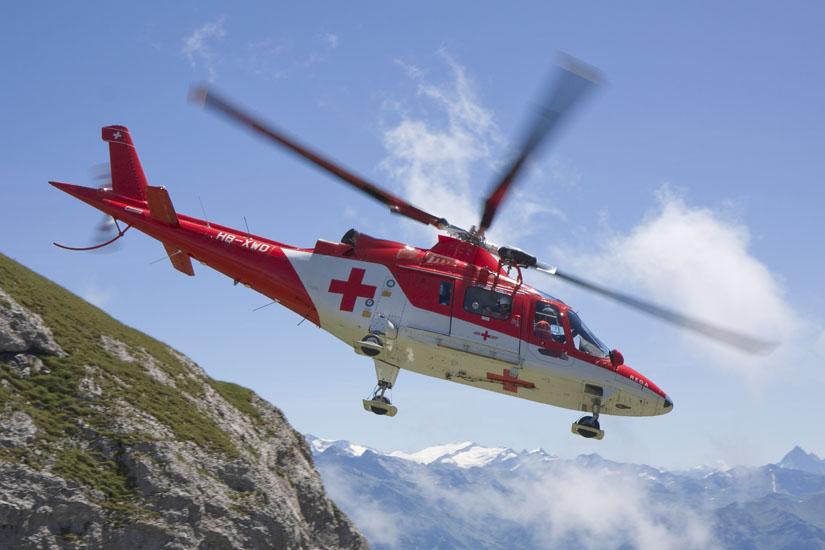 Eine A109 K2 der REGA im Flug in den Alpen
