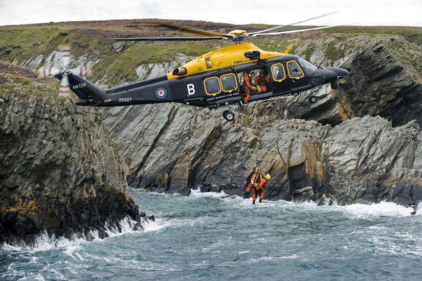 Eine AW 139 der britischen Royal Air Force (RAF) während einer Übung mit der Seilwinde vor der Küste